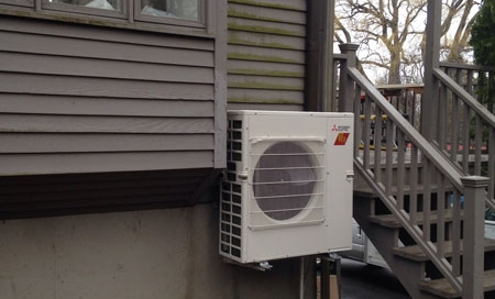 The outdoor portion of the ductless unit sits next to the home.